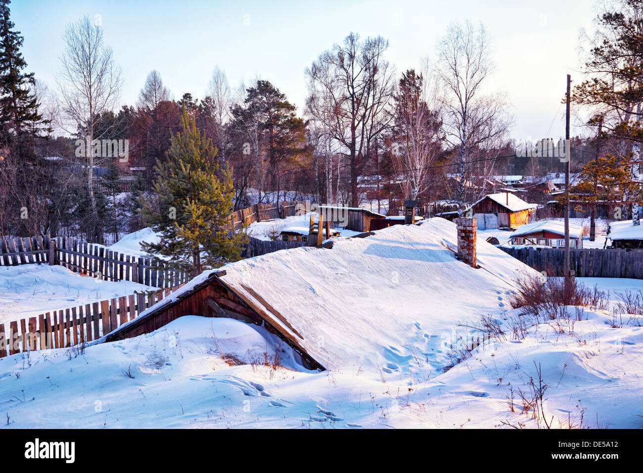 Siberian village at winter covered by snow at evening time - Stock Image