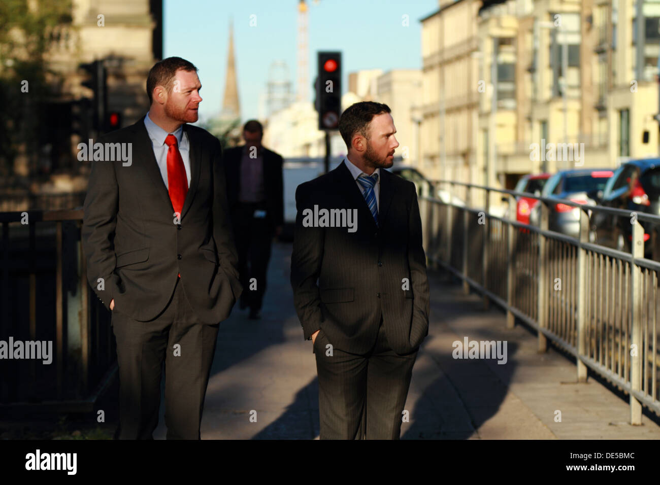 Two young men wearing suits walking to work and waiting at traffic lights to cross. - Stock Image