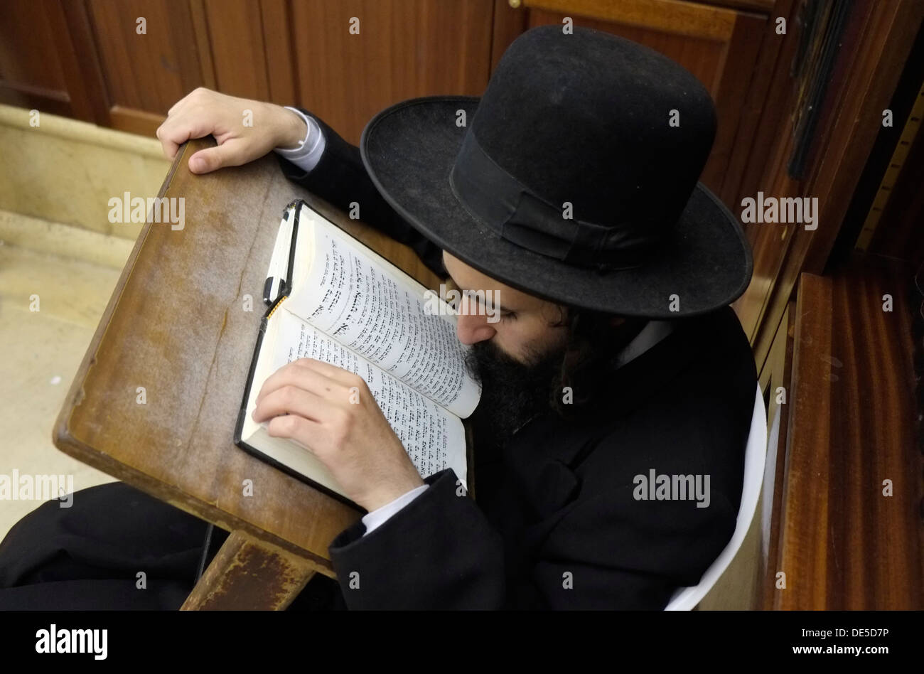 An Ultra Orthodox Jew reading the Sidur prayer book in the Synagogue of the Western Wall in East Jerusalem Israel - Stock Image