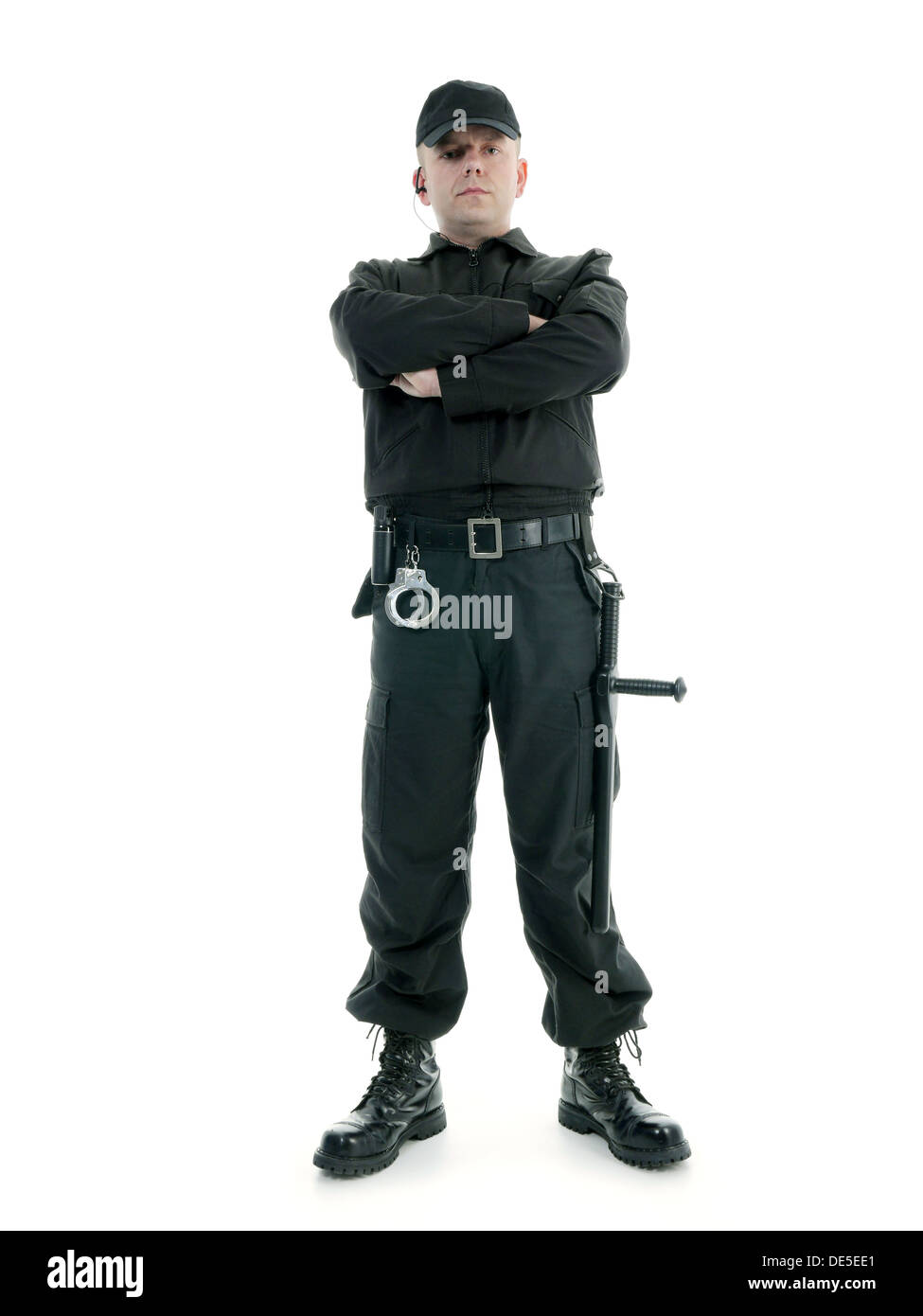 Security man wearing black uniform equipped with police club and handcuffs standing confidently with arms crossed, shot on white - Stock Image