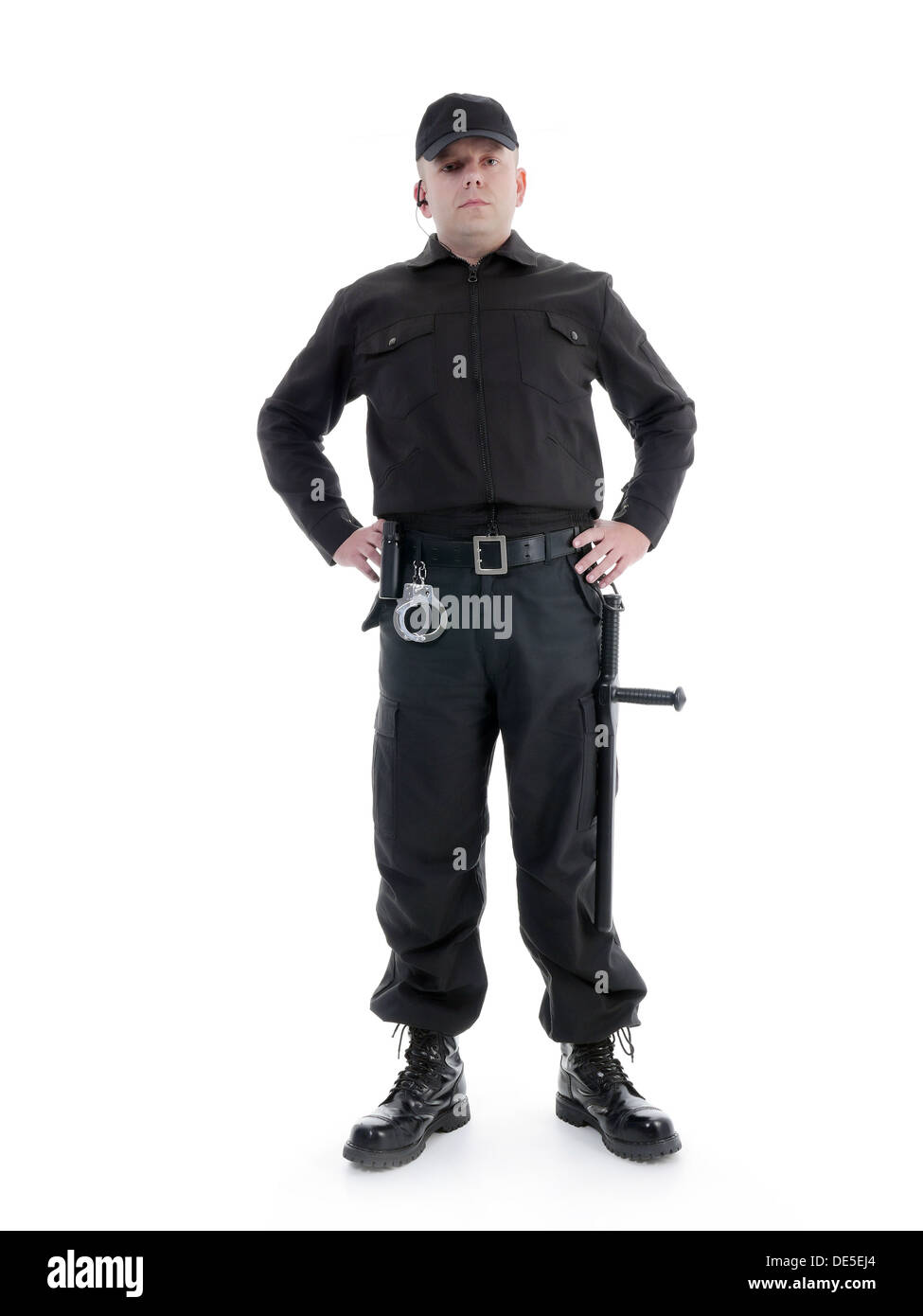 Security man wearing black uniform equipped with police club and handcuffs standing confidently with hands resting on hip - Stock Image