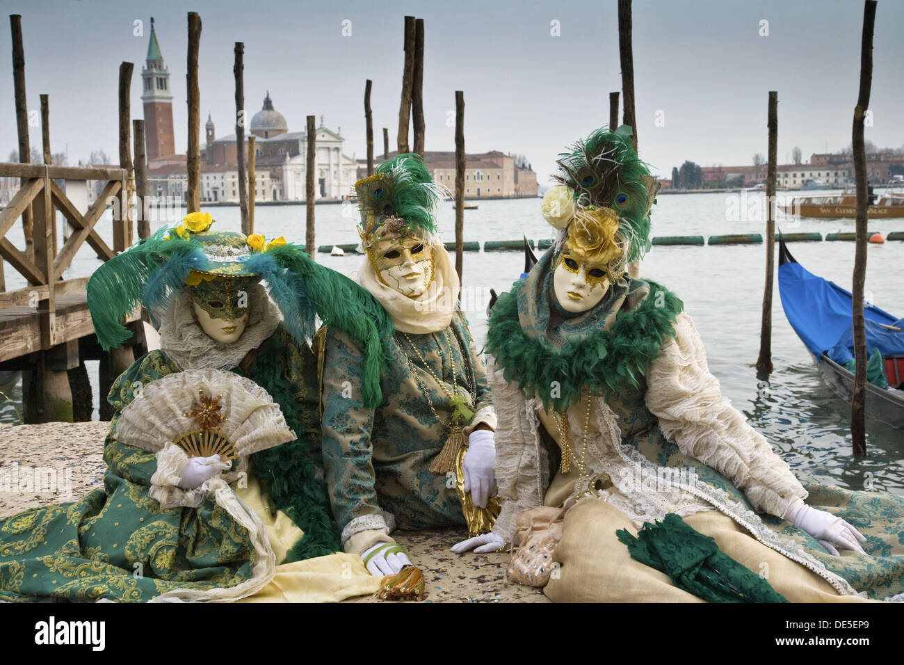 A group of masked persons at the carnival in Venice sitting at the pier in front of San Giorgio Maggiore in Venice, Italy, - Stock Image