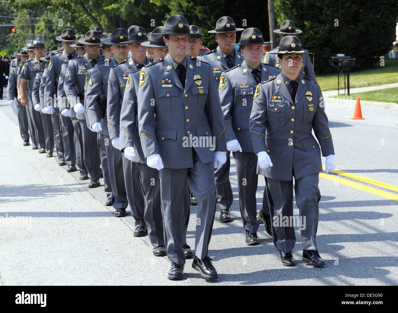 police officers march down the street at a police funeral in stock