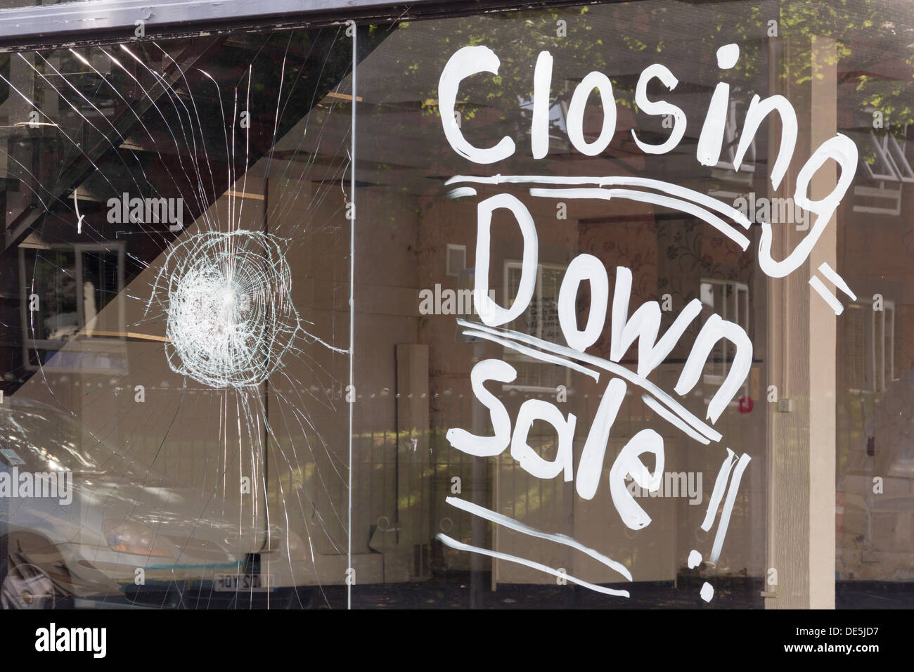 Closing down notice written in large white lettering on the shop window of an empty former furniture store showroom in Bolton. - Stock Image