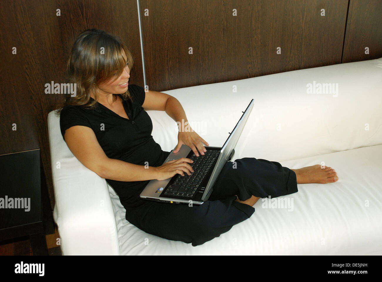 Young woman in her 30´s working comfortably on her laptop, smiling, in an office in Cadiz, Spain  White sofa and Stock Photo