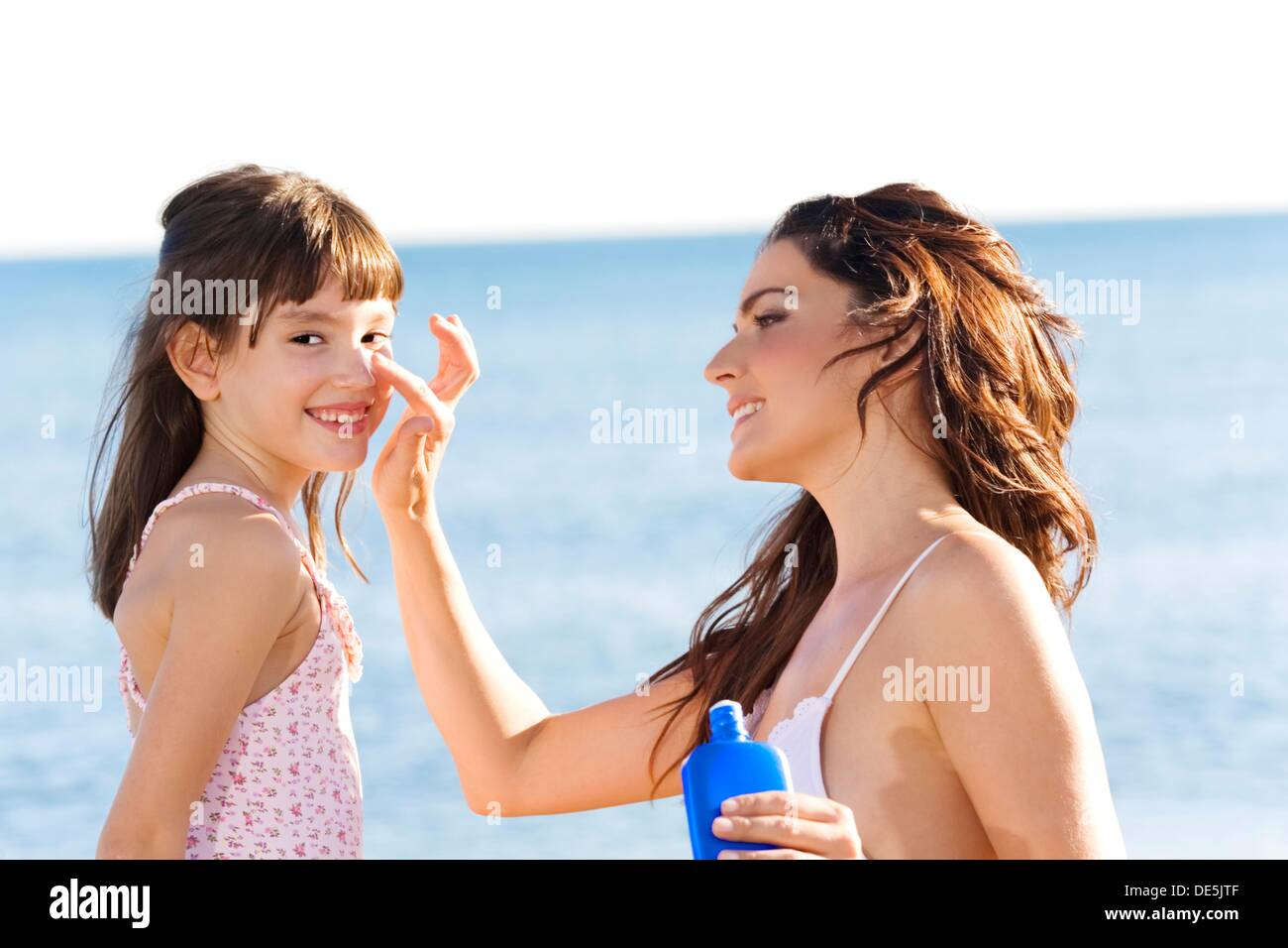 Mother applying sun protection cream to her daughter - Stock Image