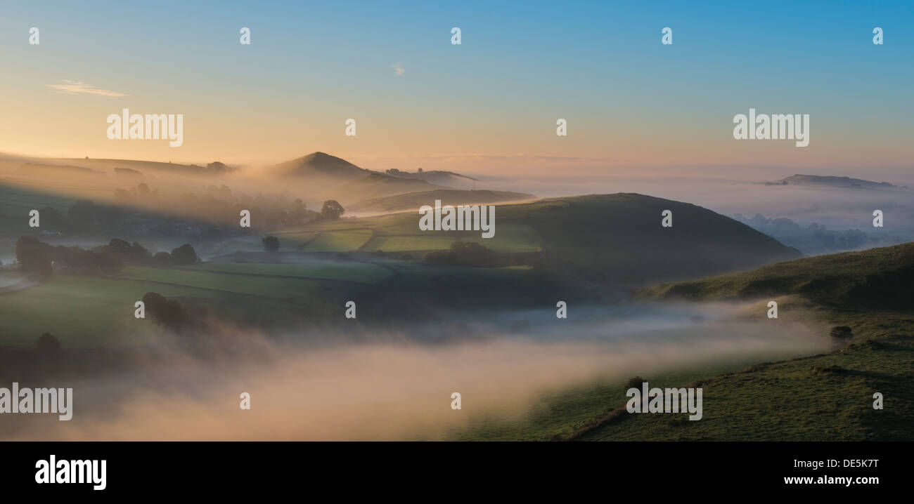 The dome shaped hill of High Wheeldon protrudes from the autumnal dawn mist in the White Peak and overlooks Earl Sterndale. - Stock Image