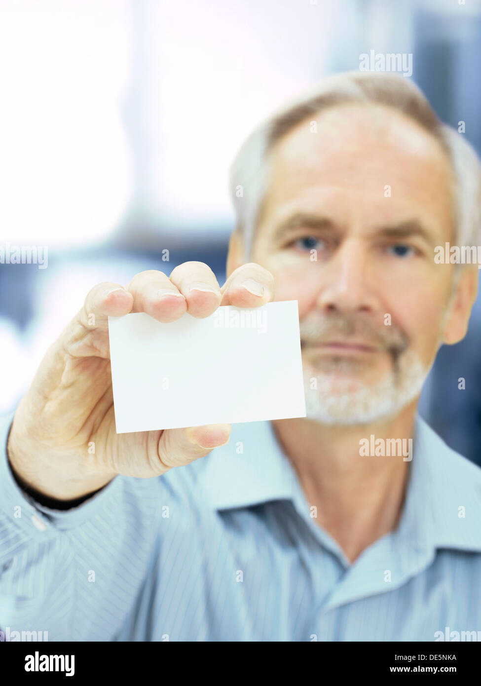 Senior, holding a blank business card - Stock Image