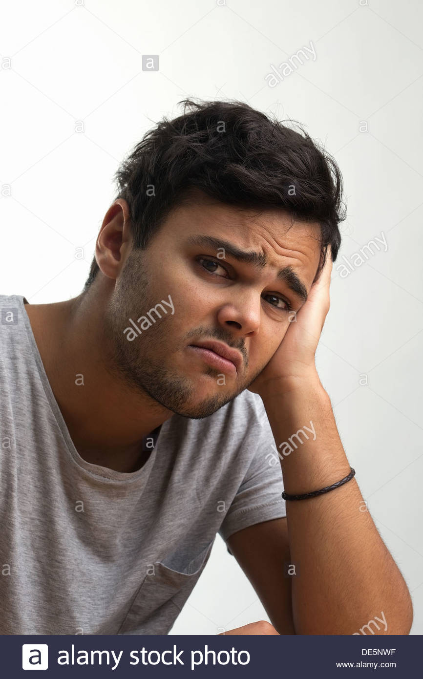 Young man in a t shirt looking worried and unhappy - Stock Image