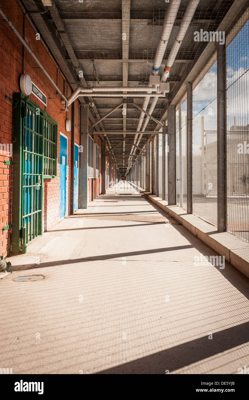 A secured external walkway at one of Her Majesty's Prisons in Lancashire, in the UK. - Stock Image
