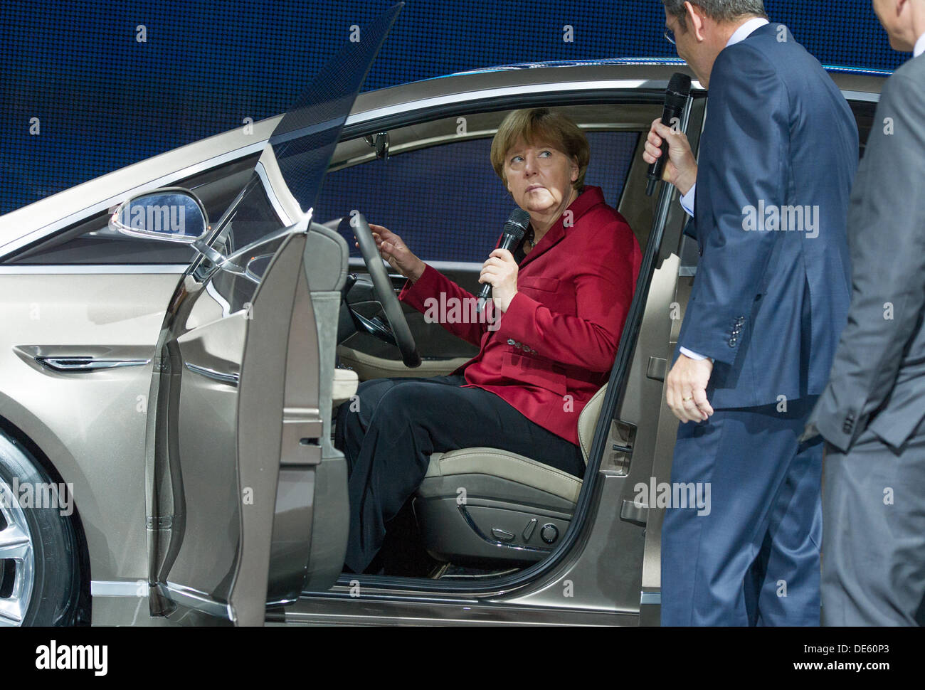 Frankfurt, Germany. 12th Sep, 2013. German Chancellor Angela Merkel (CDU, L)sits in a S-Max Concept car model of car manufacturer Ford at the 65th International Fankfurt Motor Show (IAA) in Frankfurt, Germany, 12 September 2013. Almost 1100 exhibitors from around the world present novelties at the world's largest automobile show IAA until 22 September 2013. Photo: Uwe Anspach/dpa/Alamy Live News - Stock Image