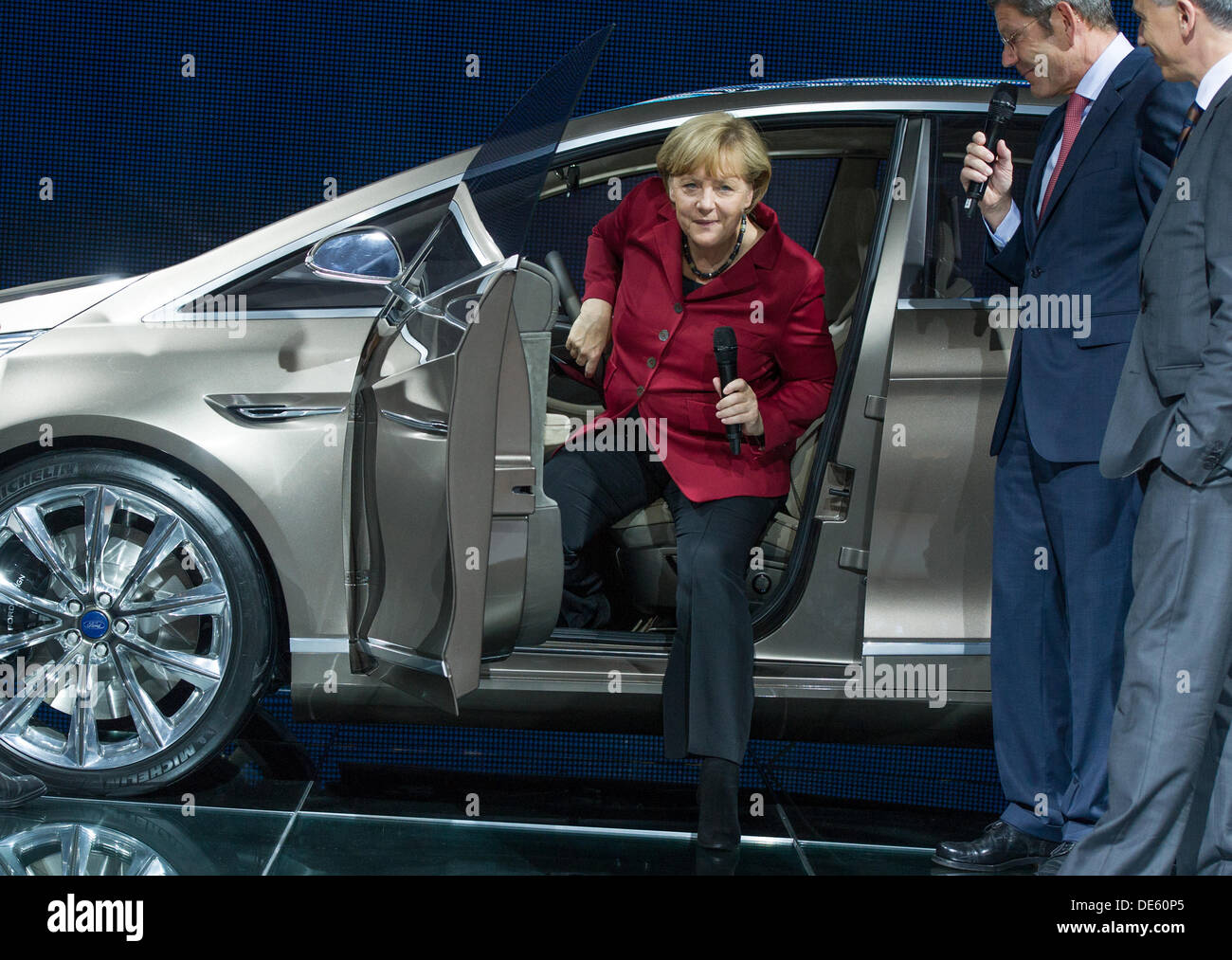 Frankfurt, Germany. 12th Sep, 2013. German Chancellor Angela Merkel (CDU, L) steps out of a S-Max Concept car model of car manufacturer Ford as the chairman of Ford Bernd Mattes (R) looks on at the 65th International Fankfurt Motor Show (IAA) in Frankfurt, Germany, 12 September 2013. Almost 1100 exhibitors from around the world present novelties at the world's largest automobile show IAA until 22 September 2013. Photo: Uwe Anspach/dpa/Alamy Live News - Stock Image