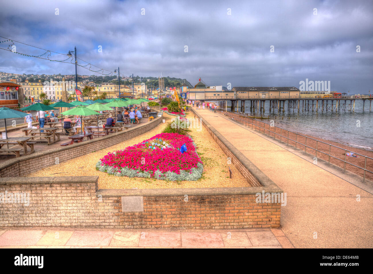 Teignmouth seafront promenade and pier Devon England, traditional English structure by the sea in HDR with red flowers Stock Photo