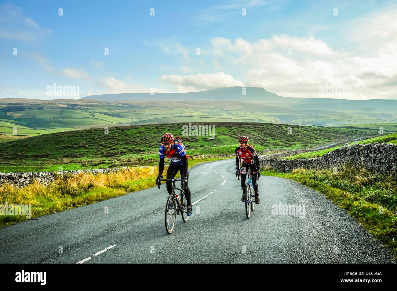 Cyclists in Ribblesdale in the Yorkshire Dales National Park with Pen-y-Ghent behind - Stock Image