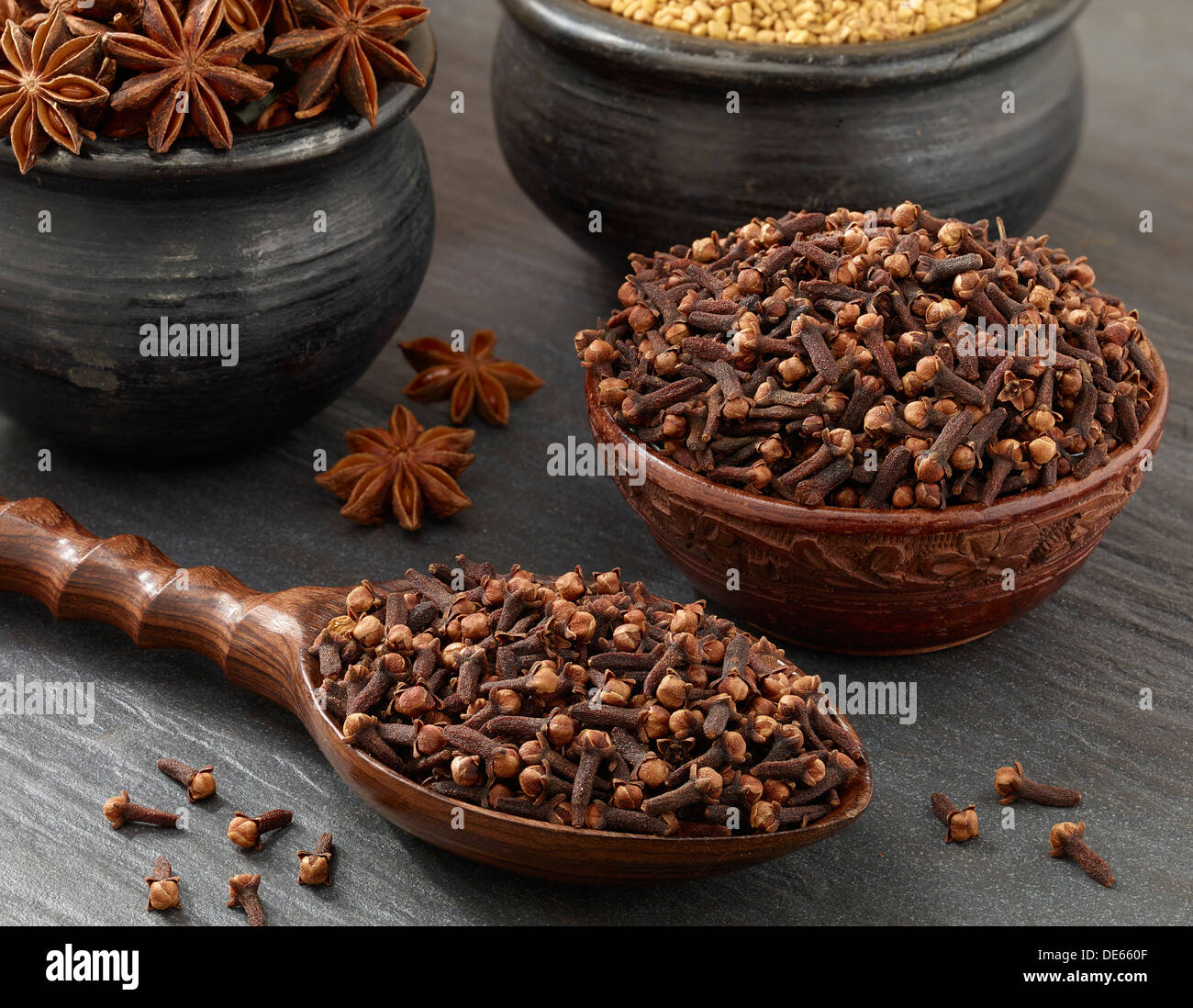 cloves(Myrtaceae, Syzygium aromaticum)  shoot in a wooden spoon and Bowls. - Stock Image