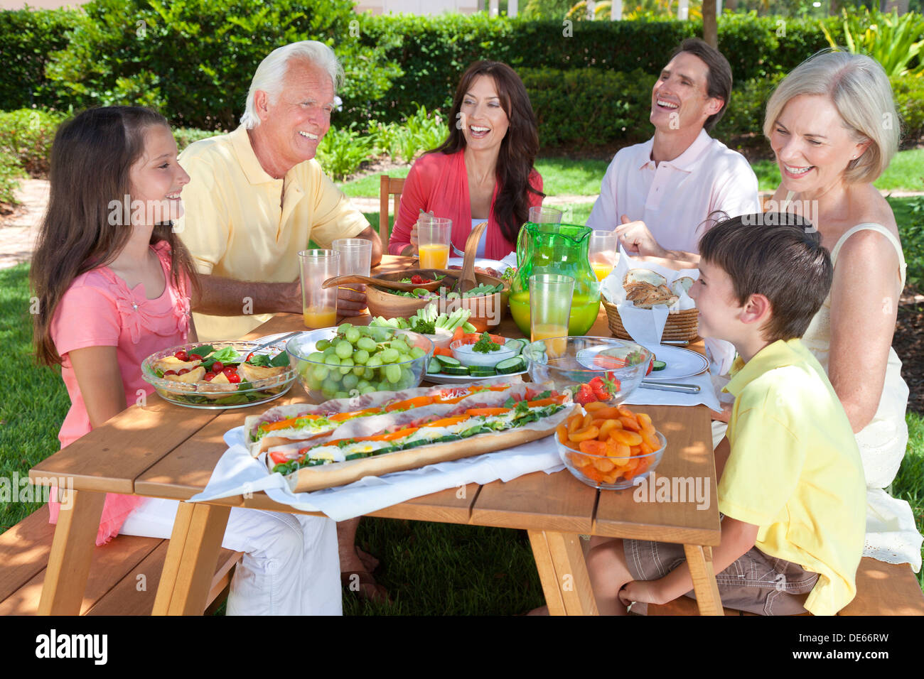 Attractive happy, smiling family of mother, father, grandparents, son and daughter eating healthy food at a picnic table outside - Stock Image