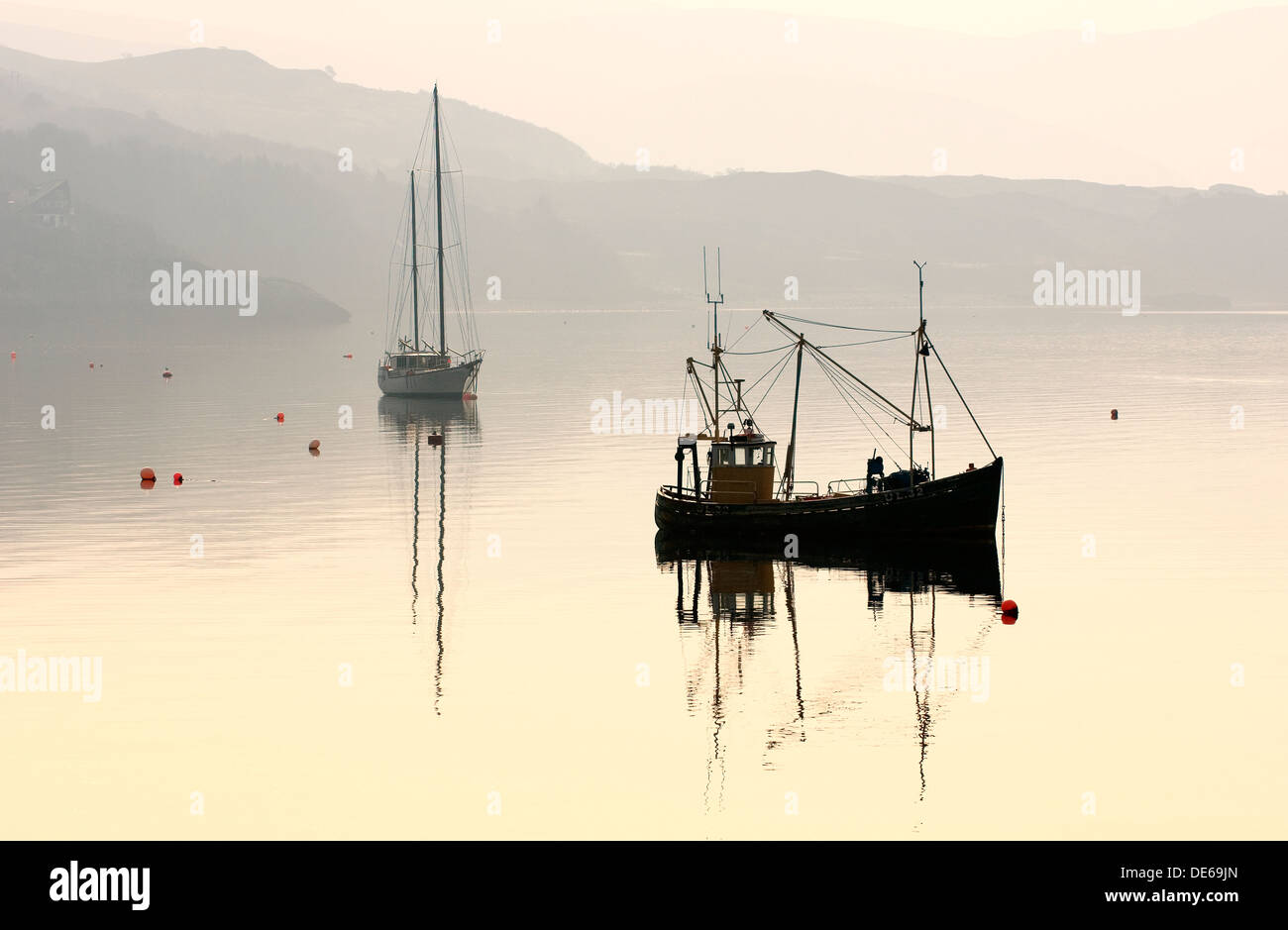 Yacht and inshore fishing boat at anchor on Loch Broom at Ullapool, Highland Region, northwest Scotland, UK. Dawn haze - Stock Image