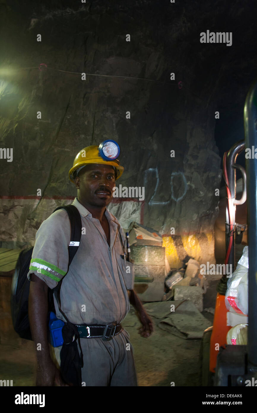 Gold miner with hard hat and safety gear in an underground mine stope - Stock Image