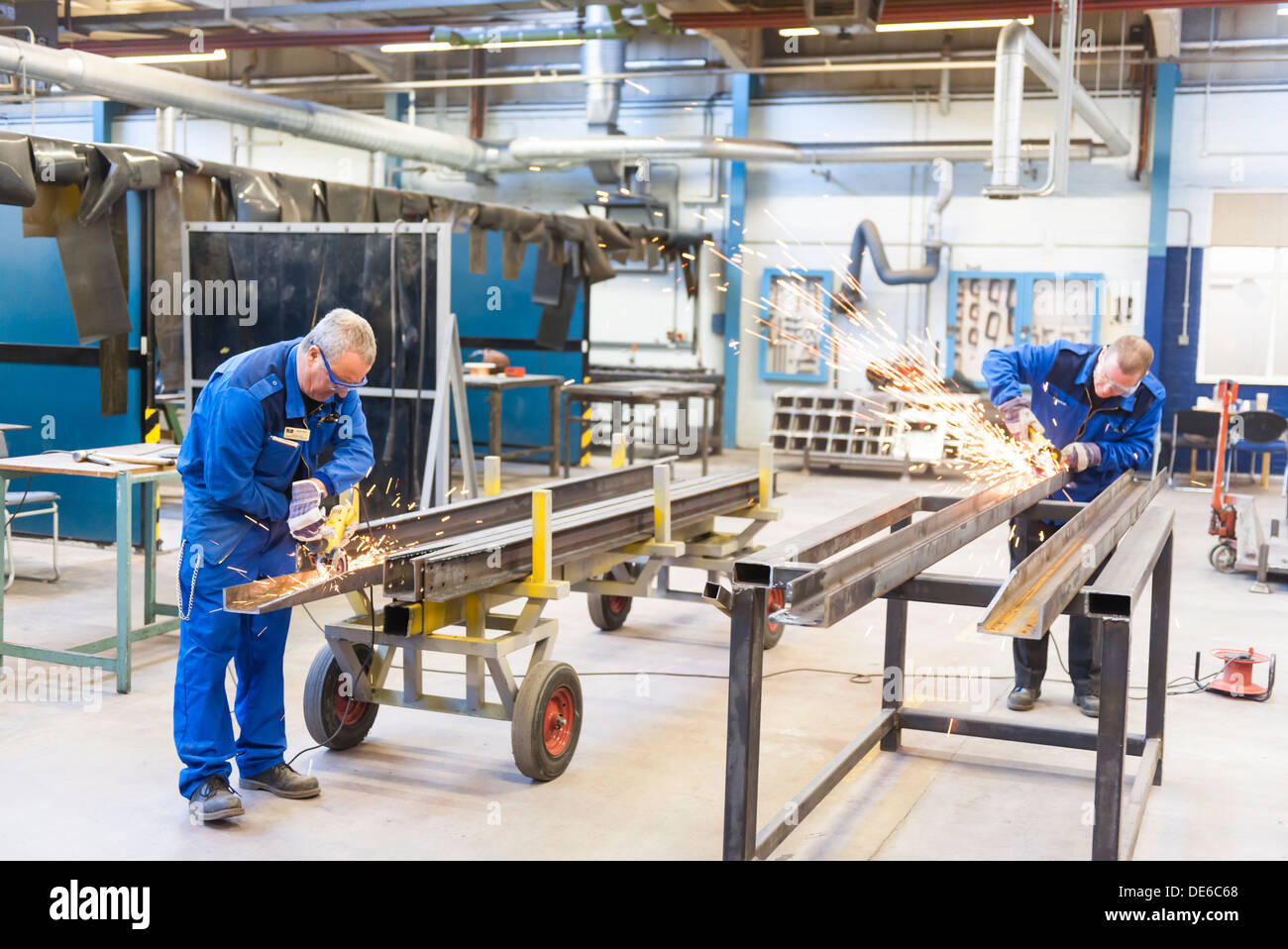 In an industrial setting, two workers craft and hone the metal extrusions for a construction project. - Stock Image