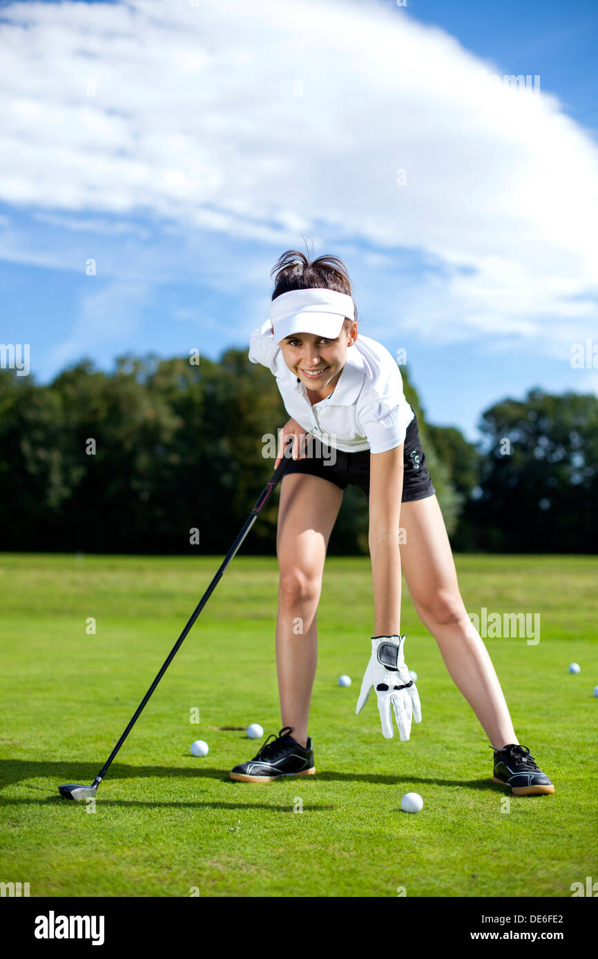 Pretty girl playing golf on grass in summer - Stock Image