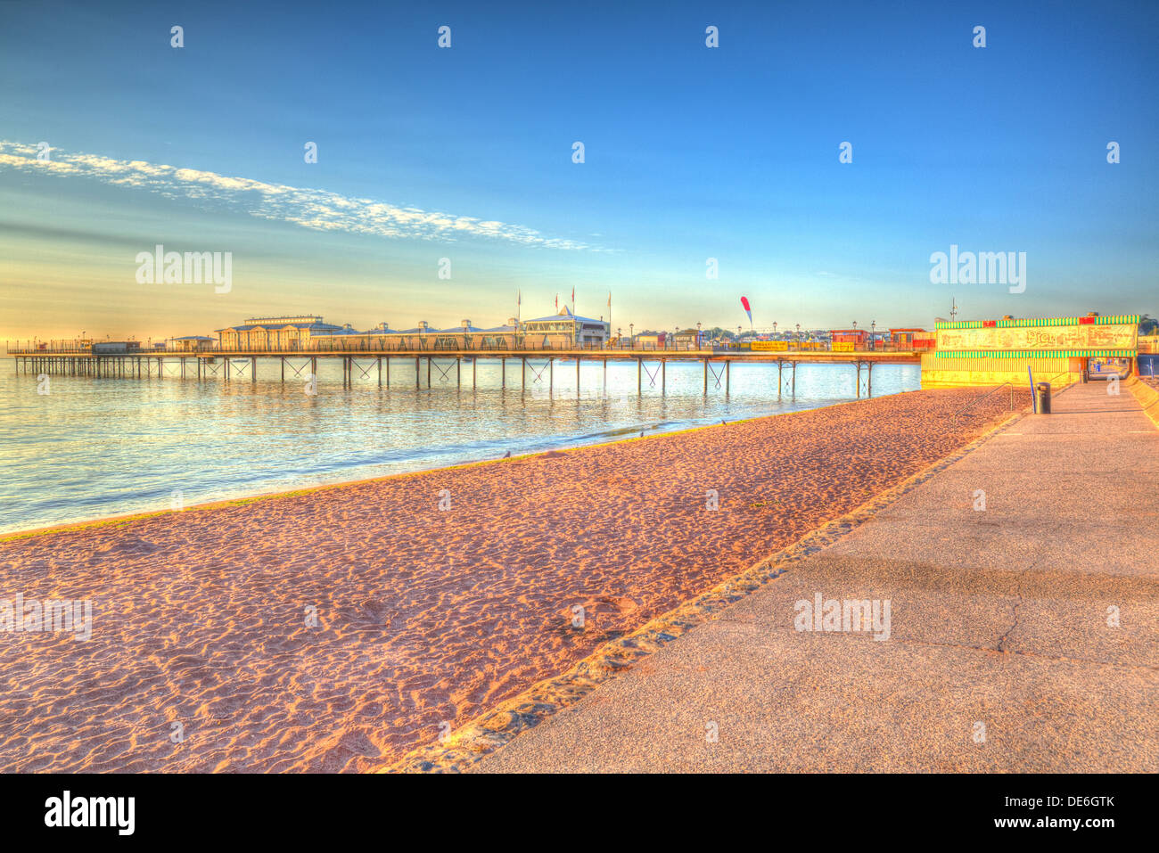 Paignton pier and sandy beach Torbay Devon England in HDR with blue sky, near tourist destinations of Torquay and Brixham - Stock Image