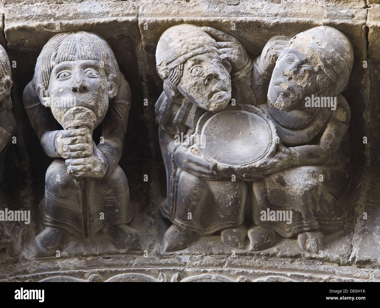 Voussoirs carved with depictions of a musician playing flute and two men holding an empty plate, Romanesque church of Santa - Stock Image