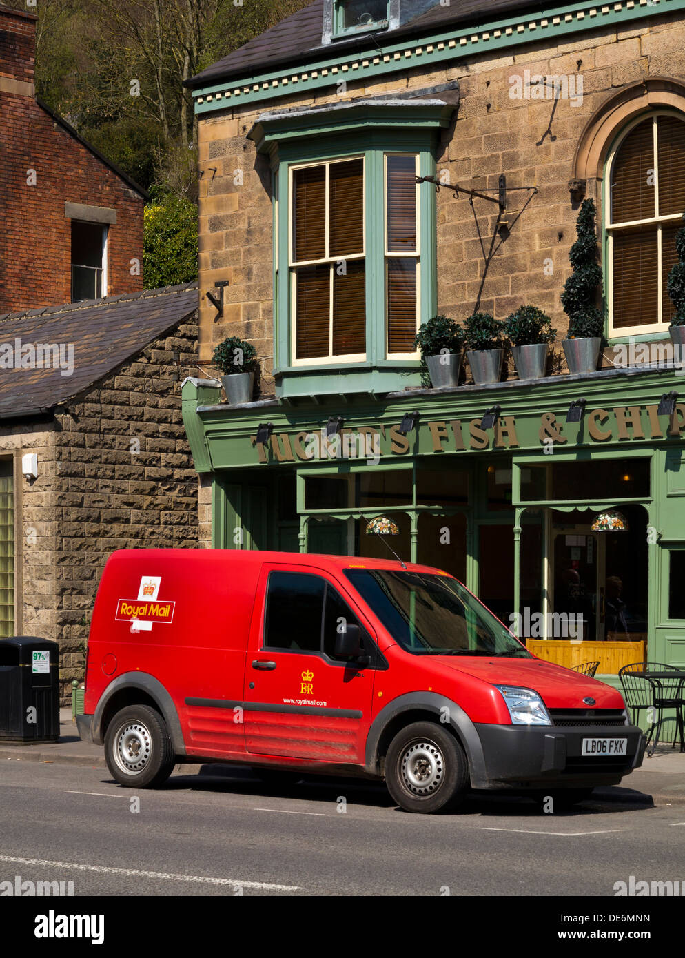 Red British Royal Mail Ford van parked whilst delivering post in a village in Derbyshire England UK - Stock Image