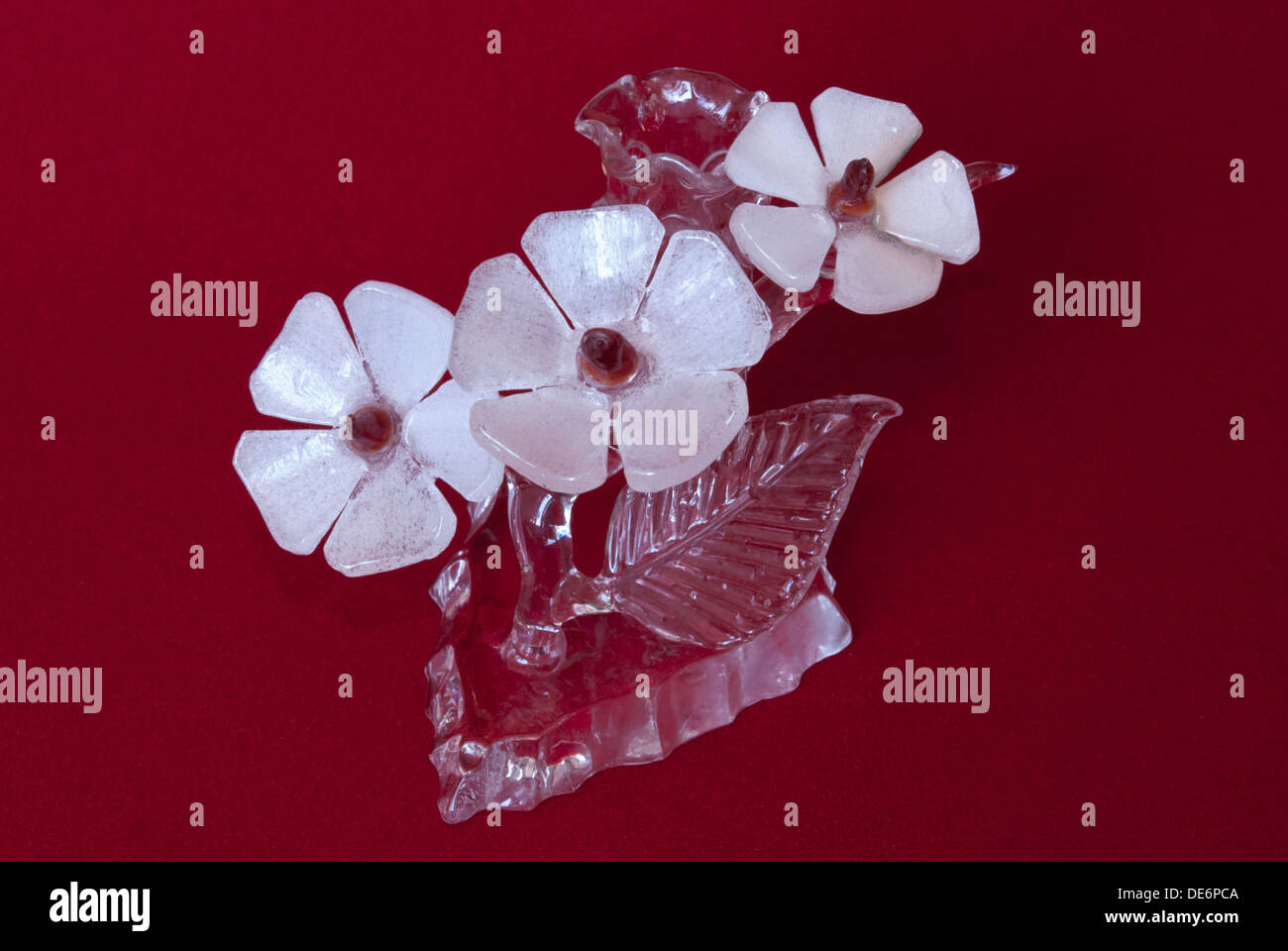 Candlestick made of rock crystal on a red background. - Stock Image