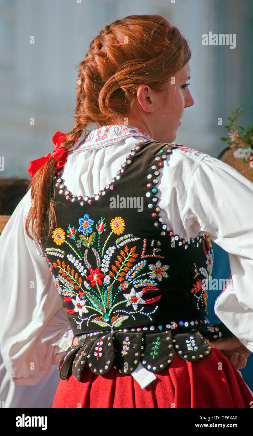 Folk dancer in Krakow's Main Market Square wearing traditional embroidered clothing. - Stock Image