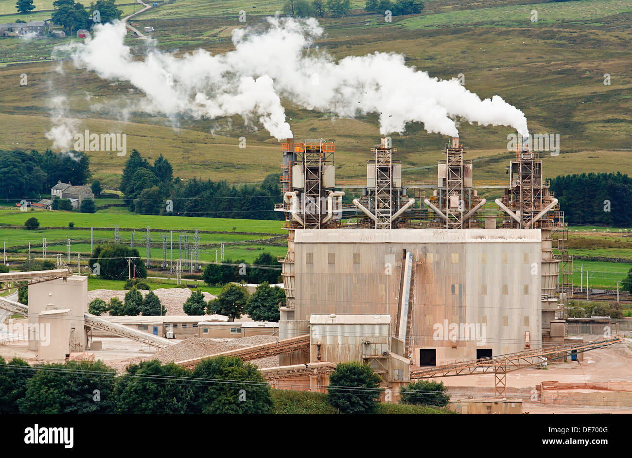 Four industrial chimneys belching smoke into the atmosphere - Stock Image
