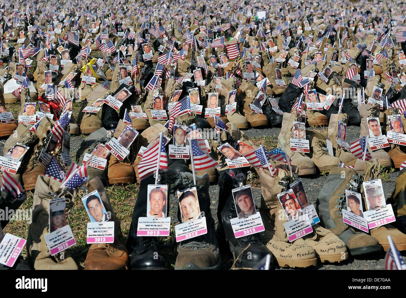Combat boots with the names and pictures of those killed in the Iraq and Afghan Wars on display on Ford Island, Stock Photo