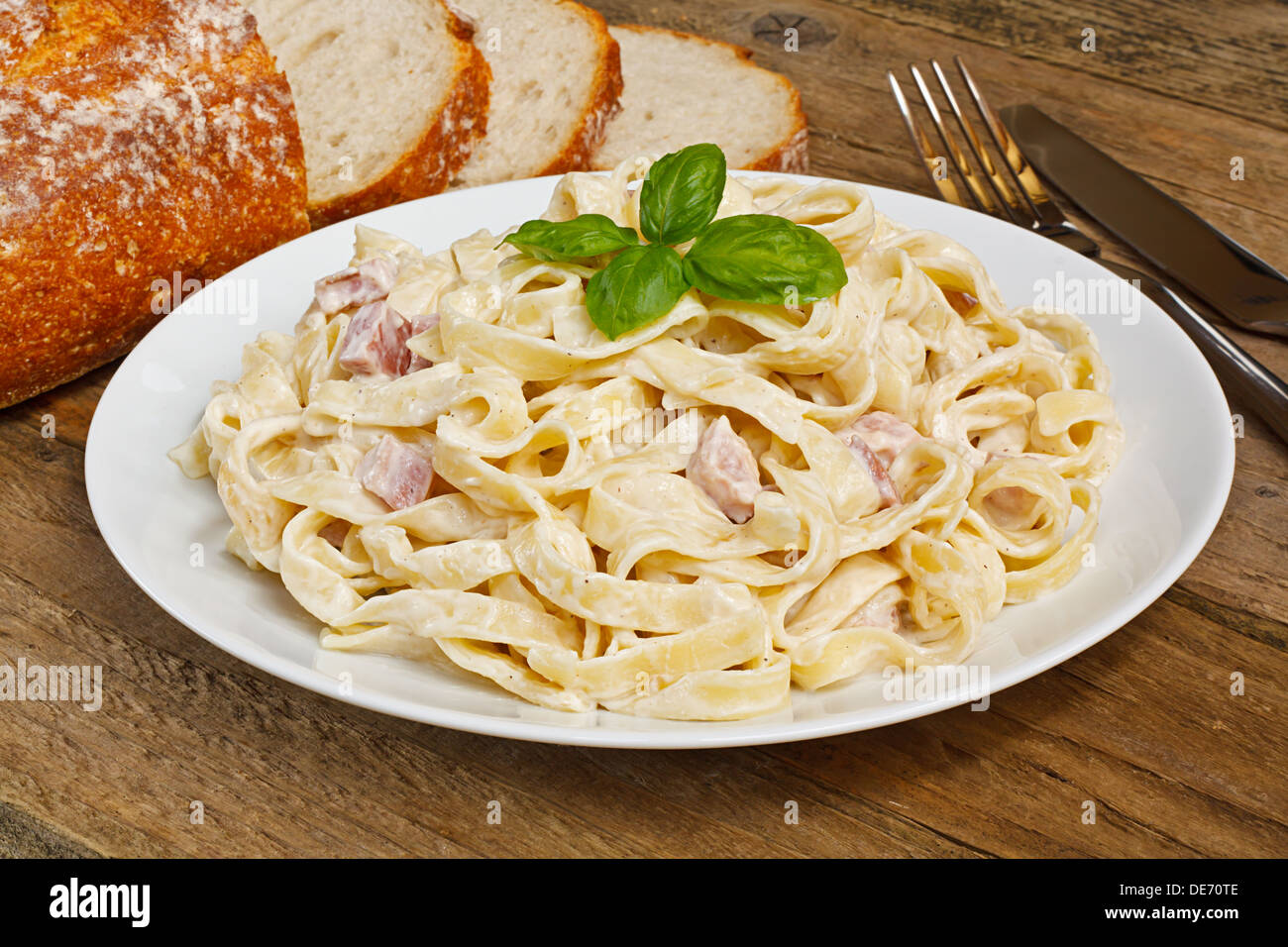 Plate of tagliatelli carbonara italian food in a rustic restaurant setting - Stock Image
