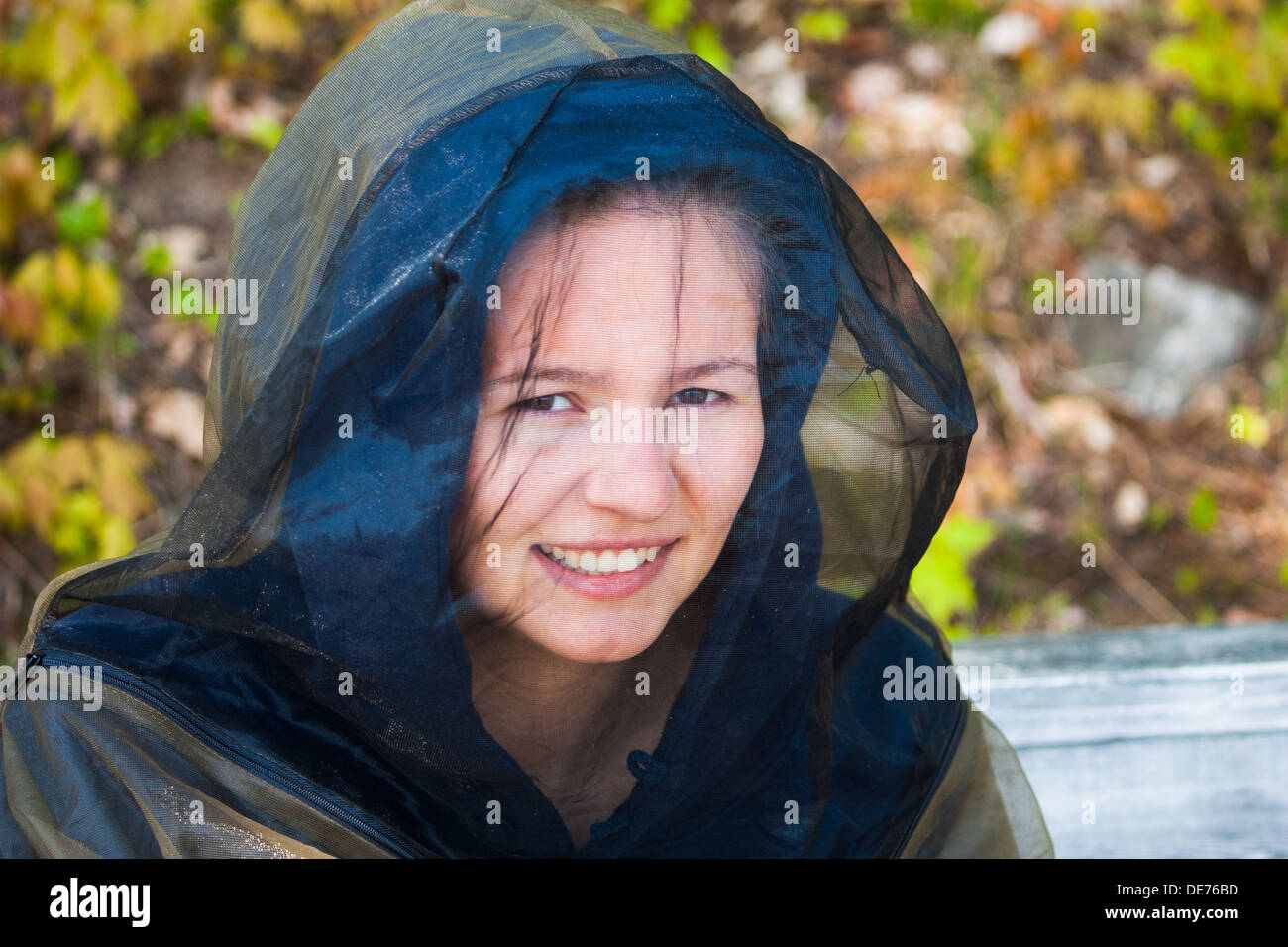 A young woman in Northern Cottage country wearing a bug shirt with screen over her face for protection from Black Flies in May - Stock Image