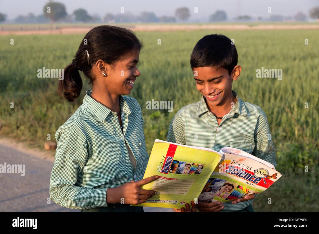 India, Uttar Pradesh, Agra, brother & sister in school uniform looking at indian textbook - Stock Image