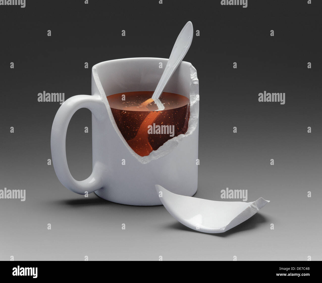 White cup with a broken part showing the liquid content inside - Stock Image