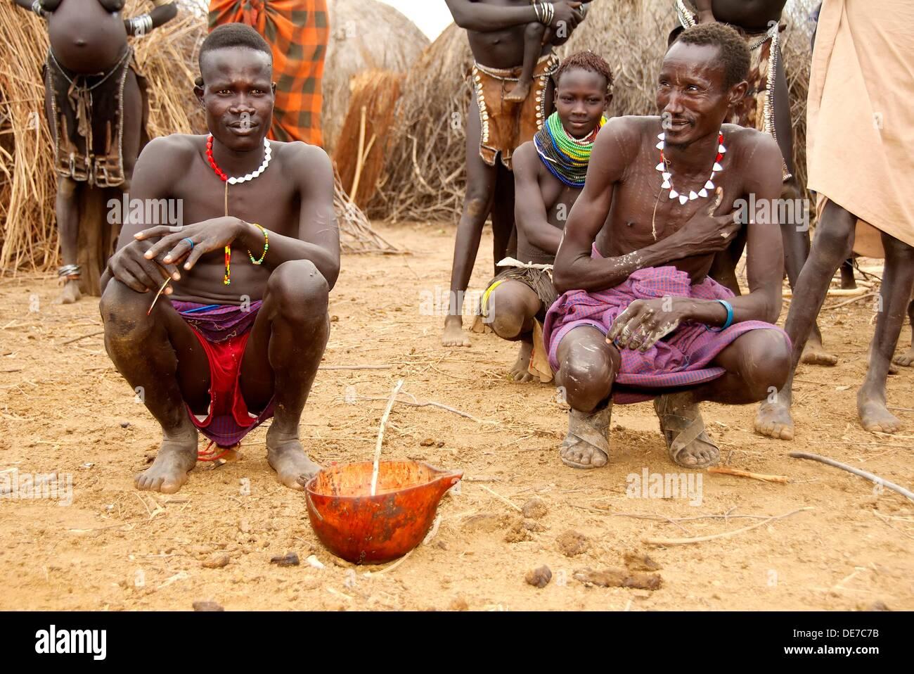 Nyangatom Bumi men sharing a calabash of cow blood, Omo river valley, Ethiopia Stock Photo