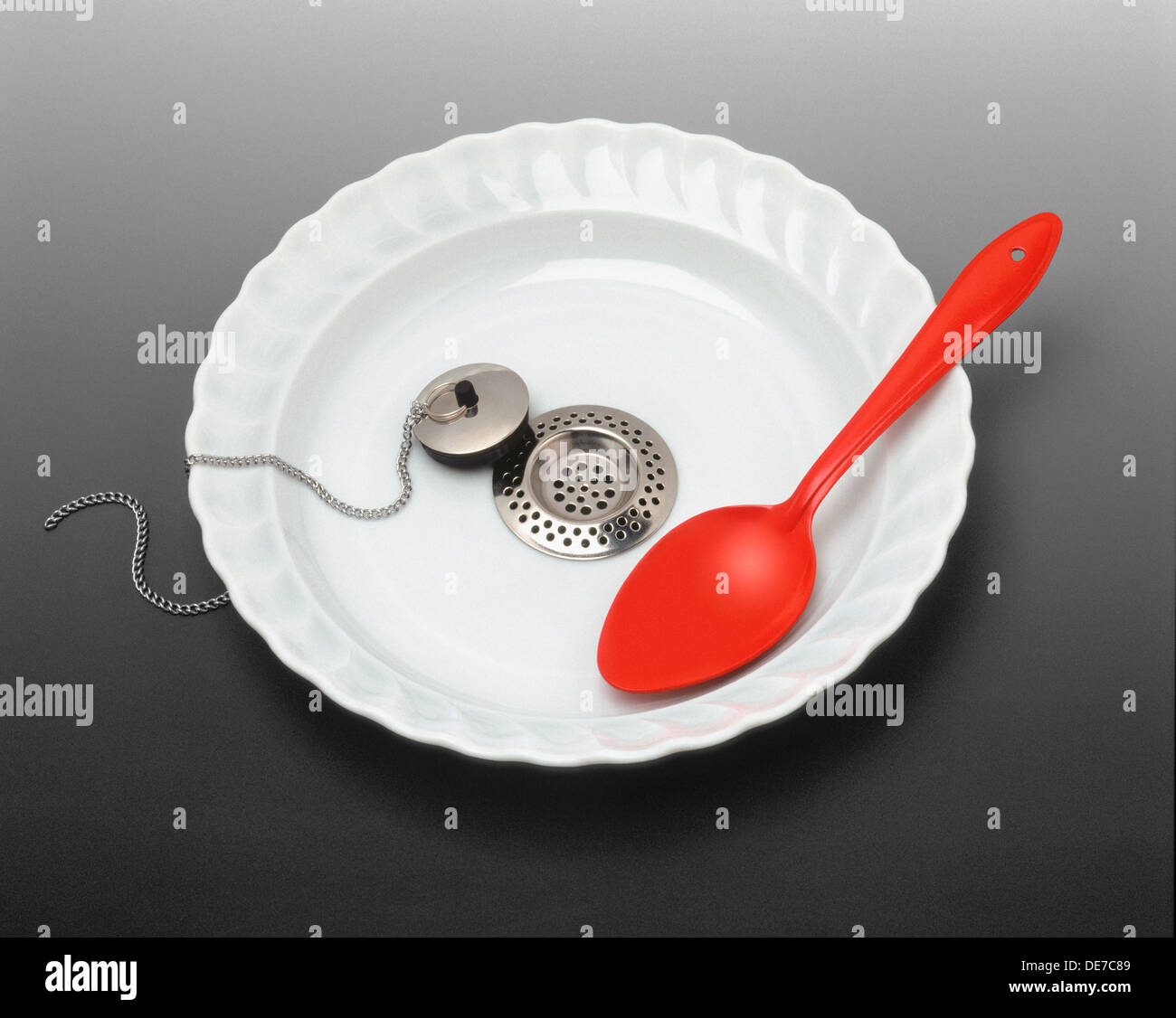 Empty plate with red spoon - Stock Image