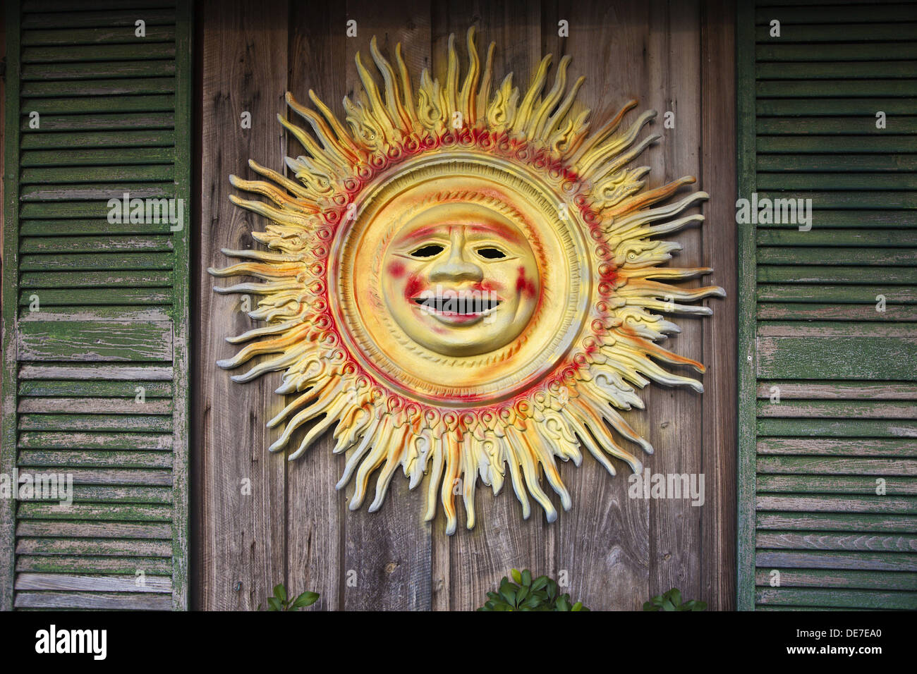 Brightly painted tin sun decoration between two green wooden ...