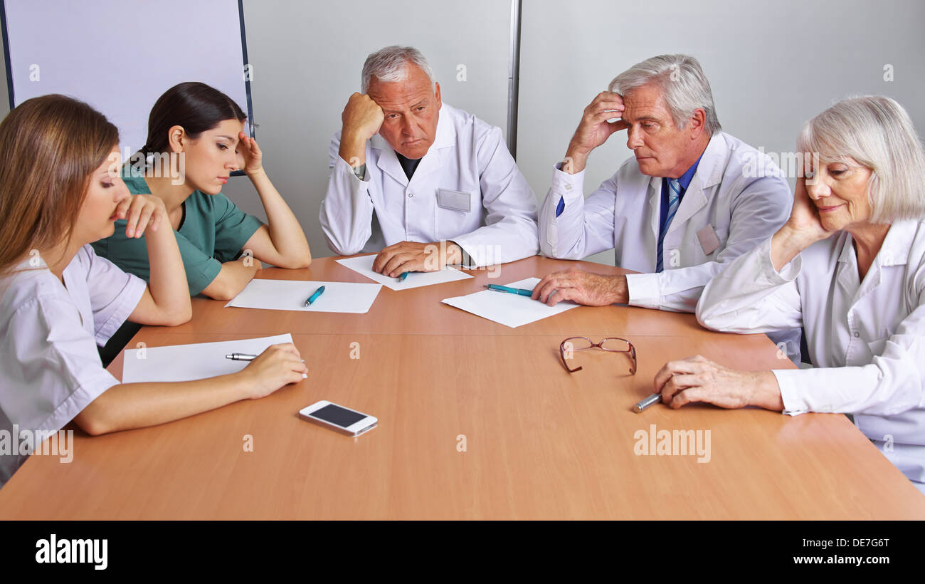 Pensive team of doctors and nurses in a meeting - Stock Image