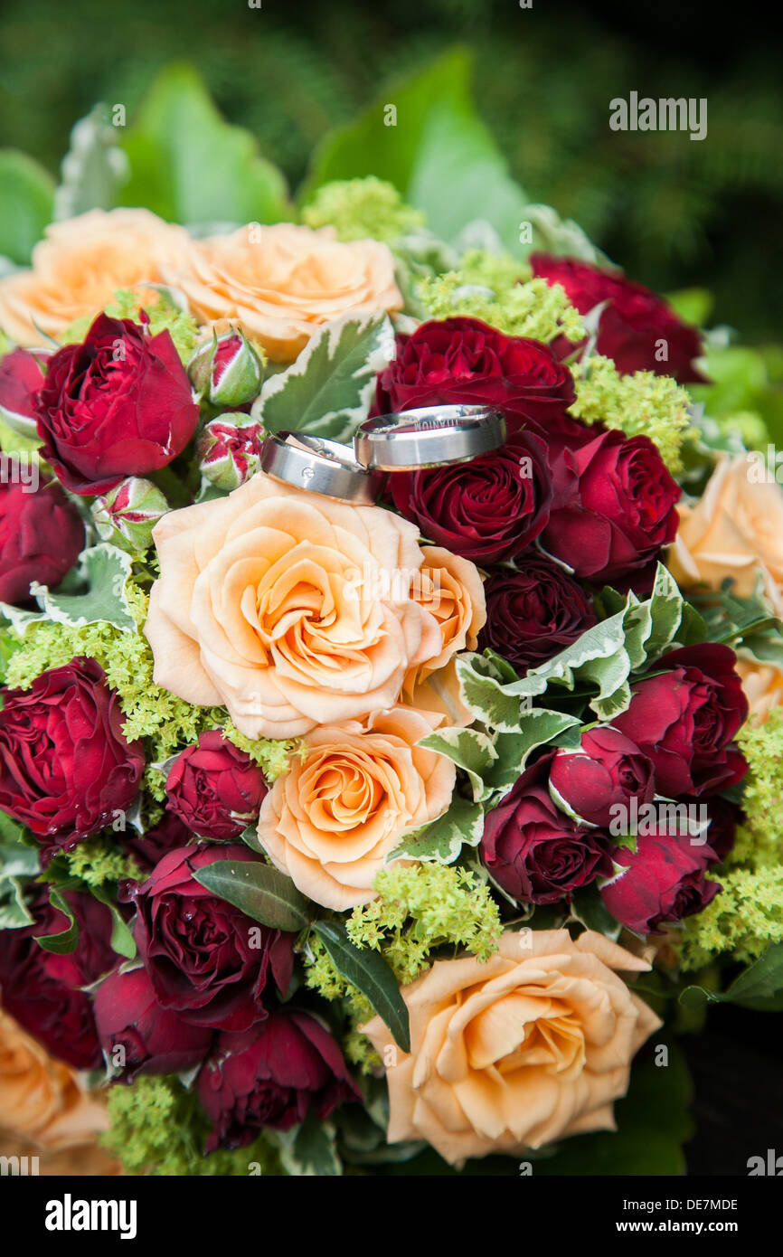Fresh Red And Yellow Roses In Bridal Flowers With Wedding Rings On