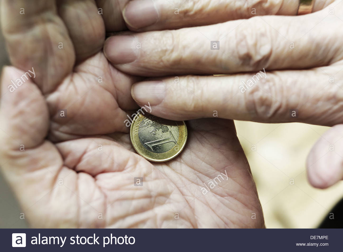 Germany, North Rhine Westphalia, Cologne, Senior woman holding one Euro coin, close up - Stock Image
