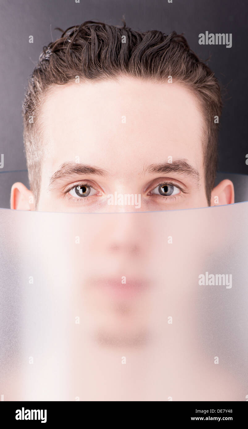 Futuristic portrait of handsome young man inside transparent tube - Stock Image