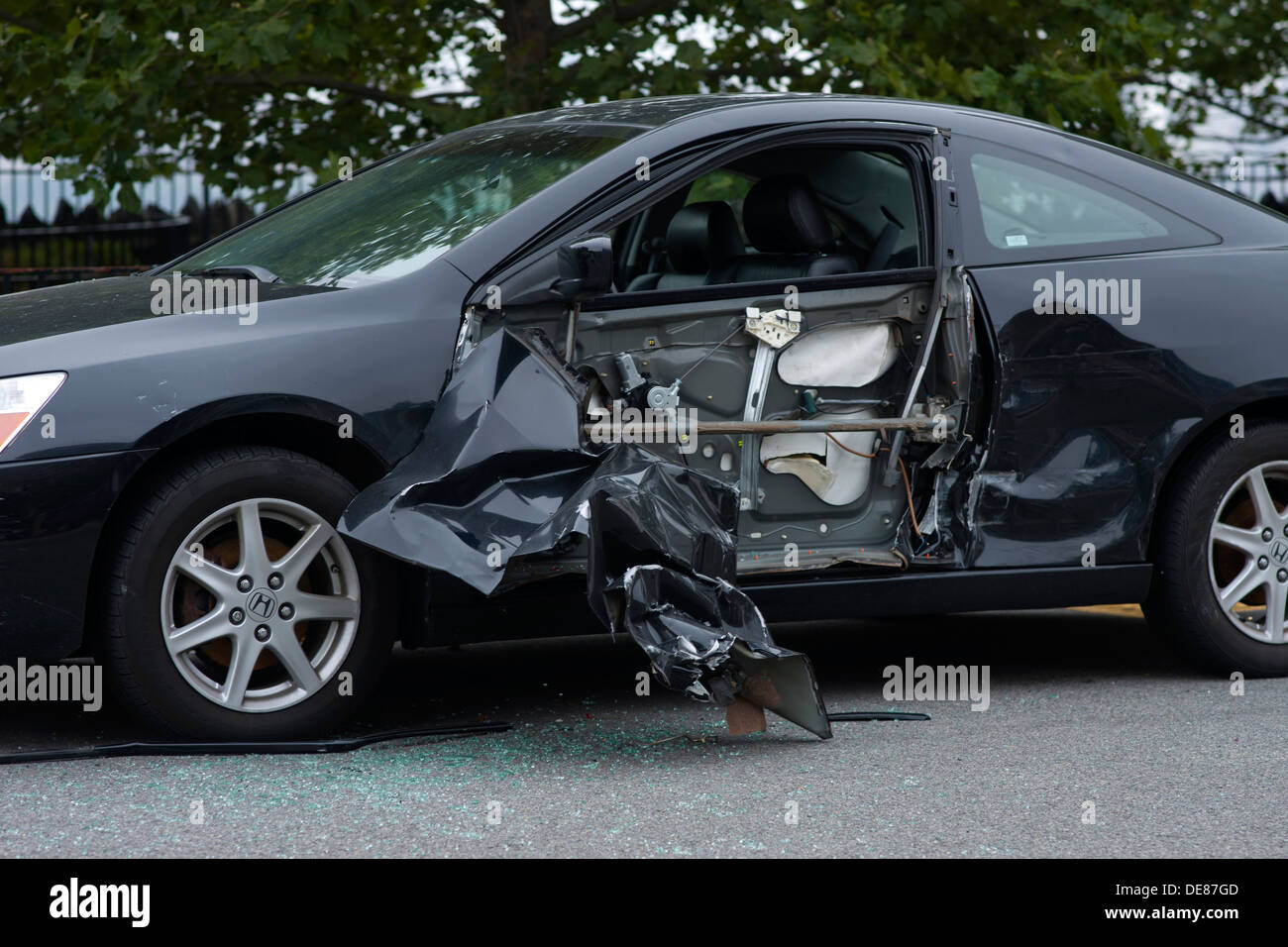 PARKED CRASHED AUTOMOBILE DAMAGED BY SIDESWIPE COLLISION ON CURVE OF ROAD - Stock Image