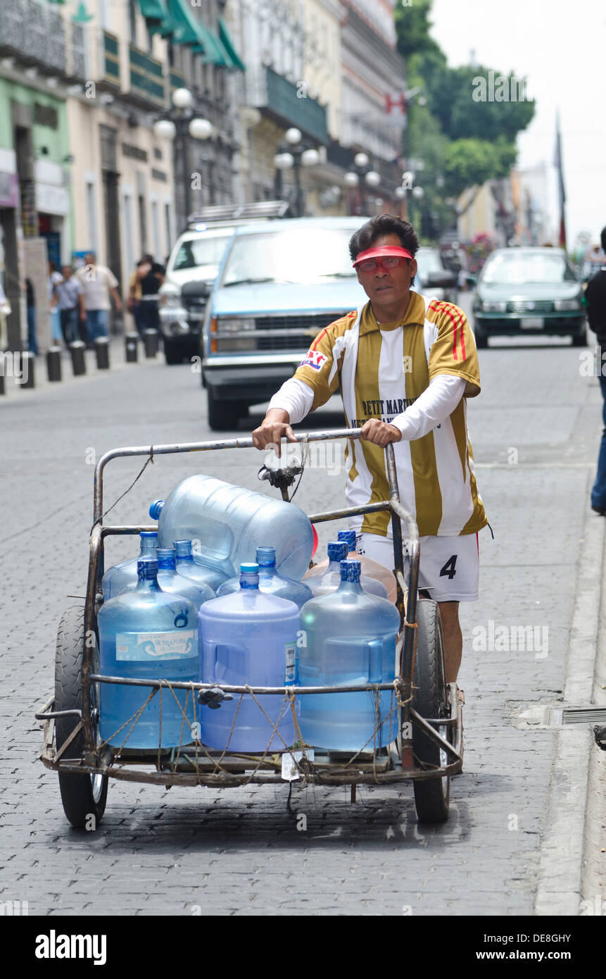 Vendor delivering large water containers on a trolley to local businesses in the centre of Puebla in Mexico - Stock Image