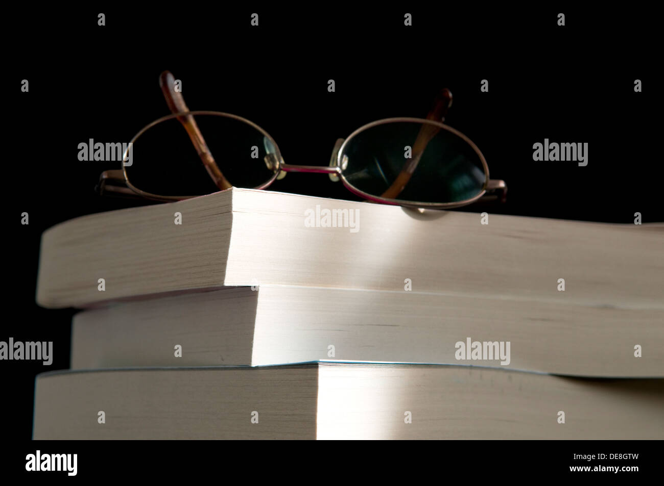 Pile of reading books on old wooden desk top, concept of learning and education, or relaxation - Stock Image