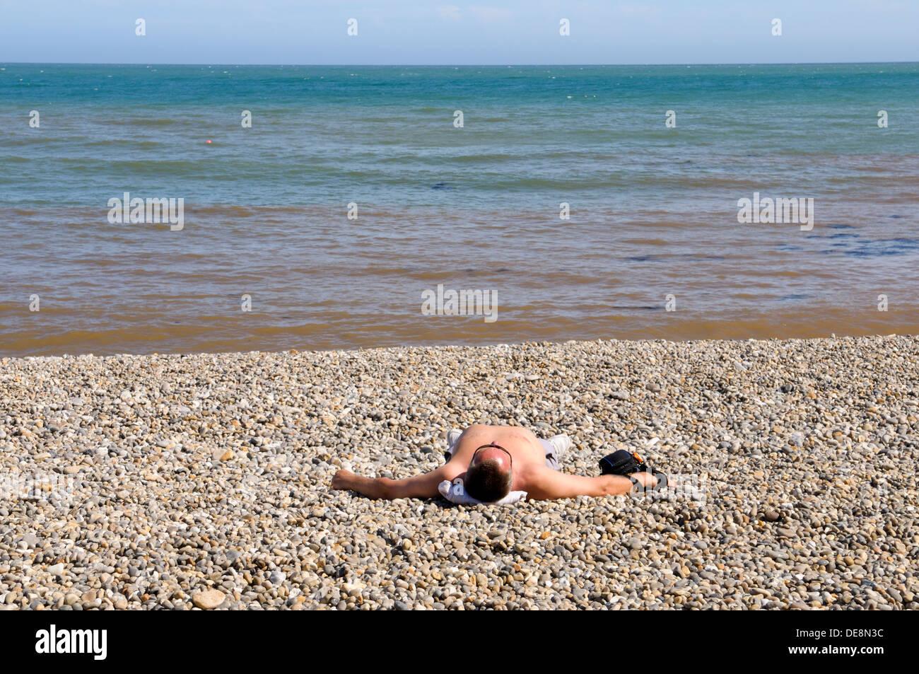 Man sunbathing on shingle beach at Beer, Devon, England, Uk - Stock Image