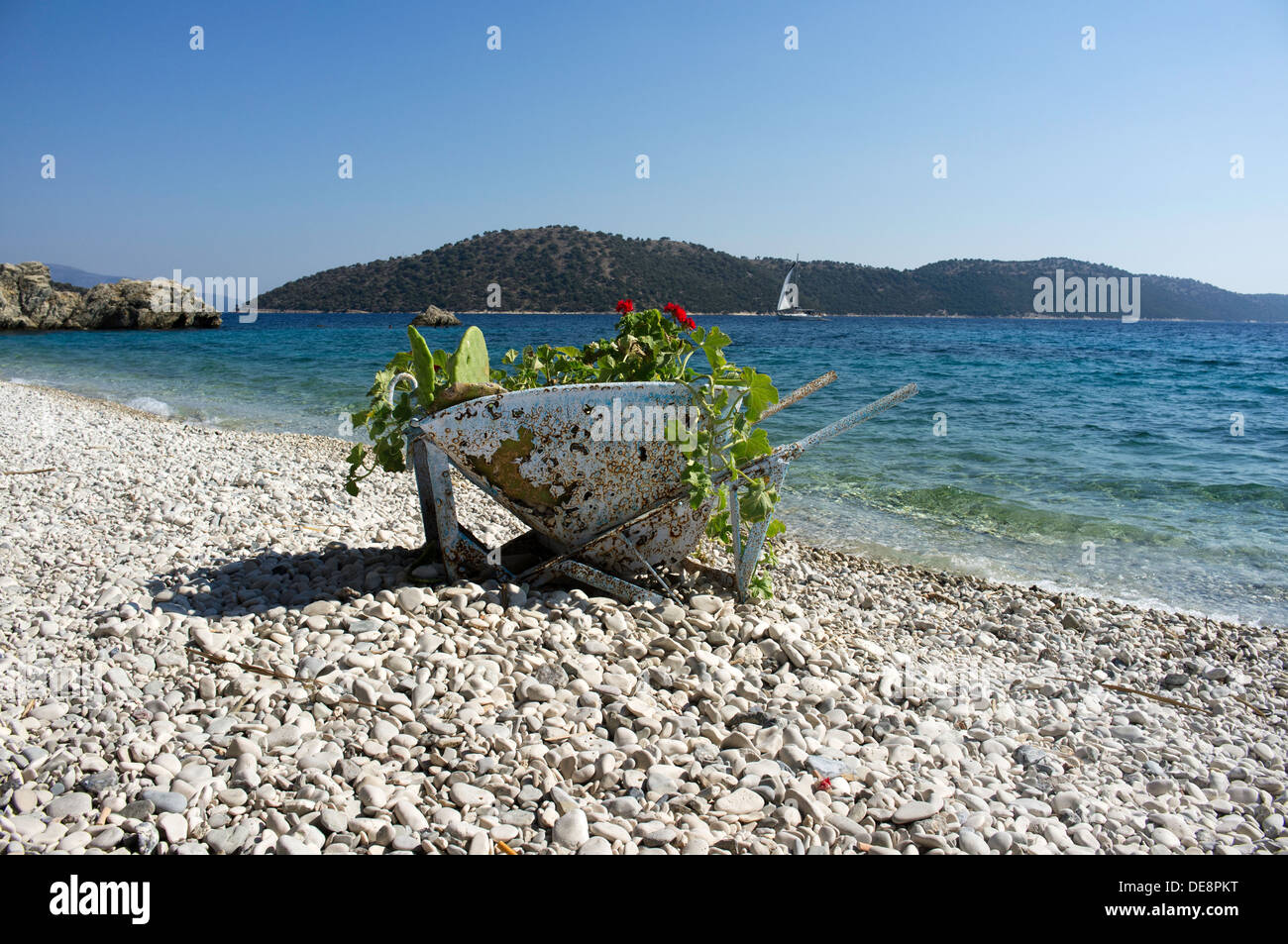 Wheelbarrow used as a simple plant container on Kalamos Town Beach.  A Sailing boat passes in front of Kastos Island. - Stock Image