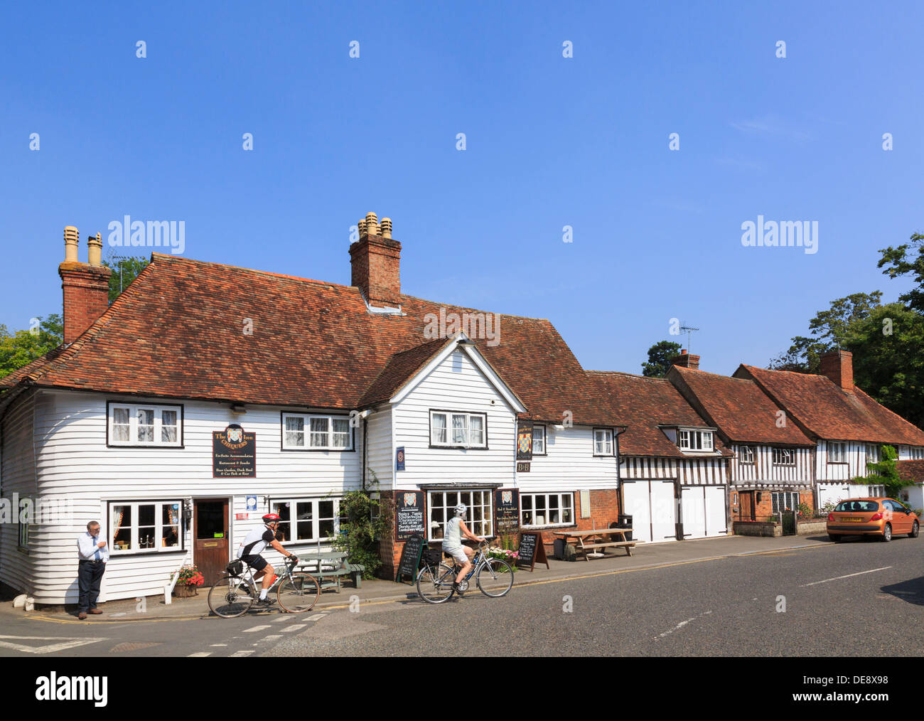 Scene with cyclists outside The Chequers Inn 14thc pub in picturesque English village The Street Smarden Kent England UK Britain - Stock Image
