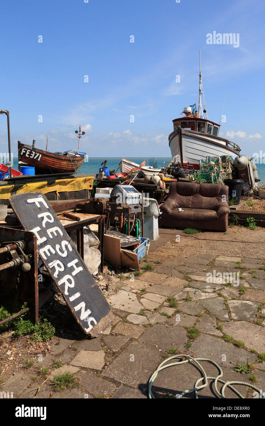 Fishing boats and sign for fresh herrings on a south coast beach seafront in Deal, Kent, England, UK, Britain - Stock Image