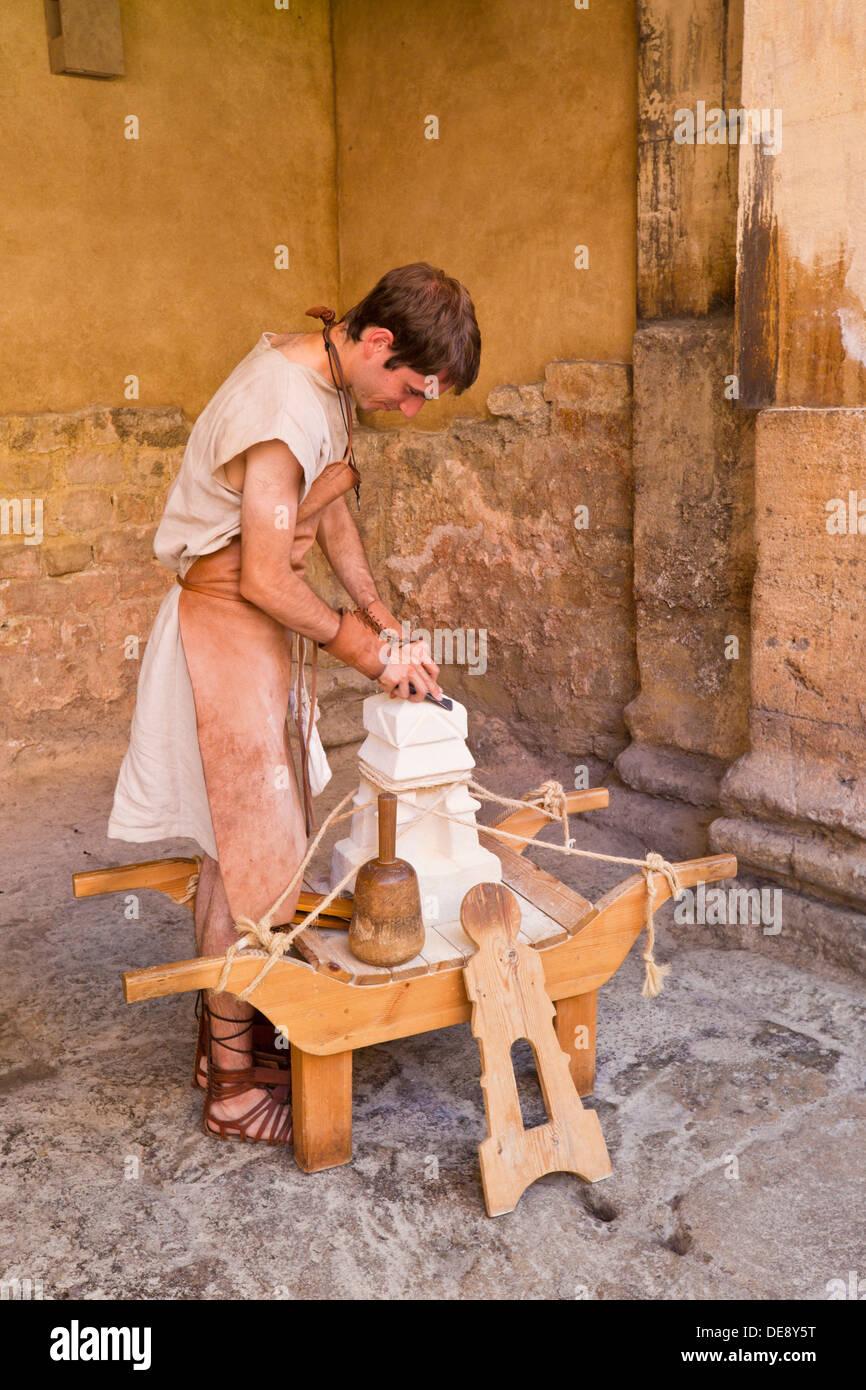 Man dressed as a roman stonemason in the Roman Baths Bath city centre north east Somerset England UK GB EU Europe - Stock Image